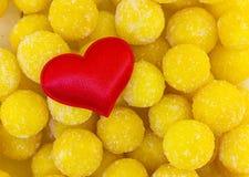 爱家庭红色心脏布料的标志在甜糖煮的黄色糖果的球背景的  基本的明信片华伦泰 免版税库存照片