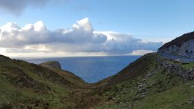 爱尔兰沿海路、海洋和被覆盖的天空 免版税库存照片