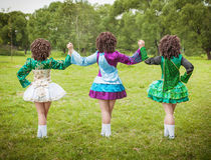 爱尔兰语的三个女孩跳舞礼服和假发摆在室外 库存照片
