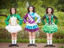 爱尔兰语的三个年轻美丽的女孩跳舞礼服和假发摆在 库存图片