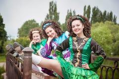 爱尔兰语的三个年轻美丽的女孩跳舞礼服和假发摆在 免版税库存照片