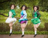爱尔兰语的三个年轻美丽的女孩跳舞礼服和假发跳舞 免版税图库摄影