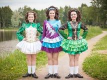 爱尔兰语的三个年轻美丽的女孩跳舞礼服摆在室外 免版税库存图片