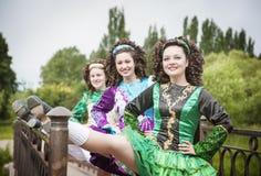 爱尔兰语的三个年轻美丽的女孩跳舞礼服摆在室外 免版税库存照片