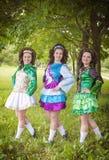 爱尔兰语的三个年轻美丽的女孩跳舞礼服摆在室外 图库摄影