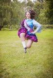 爱尔兰语的年轻美丽的女孩跳舞礼服跳室外 免版税库存图片