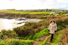 爱尔兰风景。海岸线大西洋海岸科克郡,爱尔兰。妇女走 库存图片