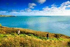 爱尔兰风景。海岸线大西洋海岸科克郡,爱尔兰。妇女走 免版税库存图片