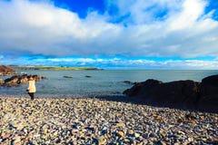 爱尔兰风景。海岸线大西洋海岸科克郡,爱尔兰。妇女走 免版税库存照片