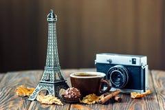 爱巴黎!罗斯、葡萄酒照相机、埃佛尔铁塔、咖啡杯、巧克力和肉桂条在木背景 St华伦泰` s日 免版税库存照片