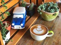 爱心脏拿铁艺术在葡萄酒木桌上的咖啡杯与蓝色陶瓷汽车 免版税库存图片