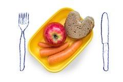 爱恋准备了饭盒用断裂面包、苹果和红萝卜在白色背景与被绘的利器 库存照片