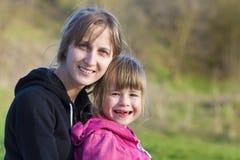 爱恋和防护地拥抱年轻美丽的白肤金发的女孩画象她的小学龄前无牙的姐妹,两个微笑的happil 免版税库存照片