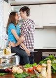年轻爱恋的人和女孩有调情的人在国内厨房 库存图片