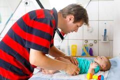 爱恋的他新出生的小女儿父亲改变的尿布  免版税库存图片