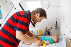 爱恋的他新出生的小女儿父亲改变的尿布  图库摄影