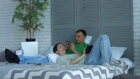 爱恋的加上放松在床上的数字式设备 股票录像