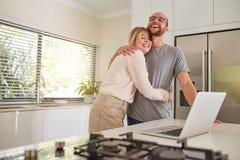 爱恋的加上膝上型计算机在厨房里在家 免版税库存照片