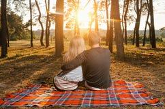 爱恋的在胳膊的夫妇坐的胳膊在床罩 免版税库存图片