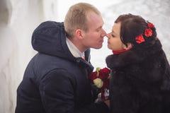 爱恋的夫妇、新郎和新娘,在街道上的亲吻在冬天 免版税库存图片