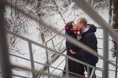 爱恋的夫妇、新郎和新娘,在街道上的亲吻在冬天 图库摄影