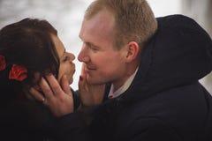 爱恋的夫妇、新郎和新娘,在街道上的亲吻在冬天 库存照片