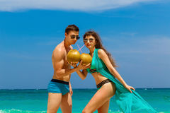 年轻爱恋的夫妇喝在热带海滩的椰子 r 免版税库存照片