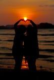 爱恋的夫妇在与太阳集合的海滩做心脏形状 免版税图库摄影