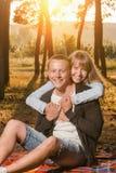 年轻爱恋的夫妇在公园坐毯子 库存图片