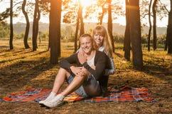 年轻爱恋的夫妇在公园坐毯子 库存照片