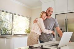 爱恋的夫妇在有膝上型计算机的厨房里 库存照片