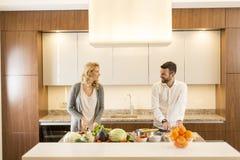 爱恋的夫妇在现代厨房里 免版税库存照片