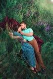 爱恋的夫妇在草甸一起说谎 免版税库存照片