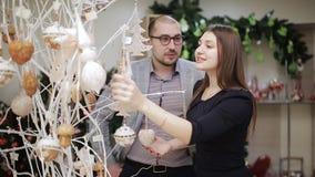 爱恋的夫妇在超级市场选择圣诞装饰 考虑圣诞节球和提议的妇女 股票视频