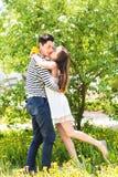 爱恋的夫妇在进展的分支春日下 年轻成人深色的亲吻在新鲜的开花苹果的男人和妇女 图库摄影