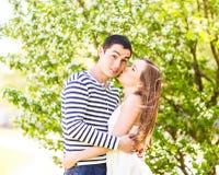 爱恋的夫妇在进展的分支春日下 年轻成人深色的亲吻在新鲜的开花苹果的男人和妇女 库存图片
