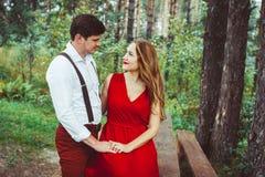爱恋的夫妇在长凳的森林里 图库摄影