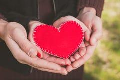 爱恋的夫妇在他们的手上的拿着红色心脏 库存照片