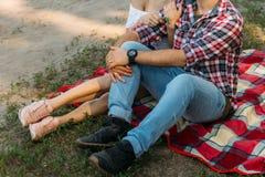 爱恋的夫妇坐在森林和容忍的红色格子花呢披肩 E 库存图片