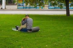 年轻爱恋的夫妇坐在绿色草坪的地面垫德聂伯级河堤防的 免版税库存图片