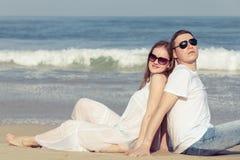 爱恋的夫妇坐海滩在天时间 库存照片