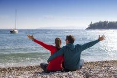 爱恋的夫妇坐海滩 免版税库存图片
