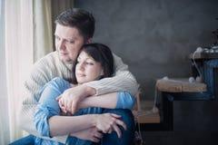 爱恋的夫妇坐的拥抱在用圣诞节诗歌选装饰的楼梯 免版税图库摄影