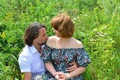爱恋的夫妇坐草在夏天 库存图片