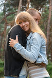 爱恋的夫妇拥抱在森林的,女孩微笑 免版税库存图片