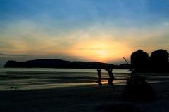爱恋的夫妇的剪影,跳跃在海滩在日落 免版税库存照片