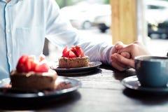 爱恋的夫妇的手在咖啡馆的桌上 库存图片