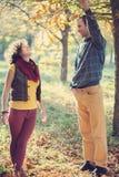 爱恋的夫妇获得乐趣在秋季公园 库存图片