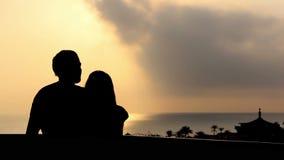 爱恋的夫妇跳舞和拥抱的剪影在日落的海附近
