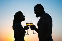 爱恋的夫妇饮用的酒或香槟在日落时间,一加上的剪影葡萄酒杯在日落背景,人和 免版税库存照片
